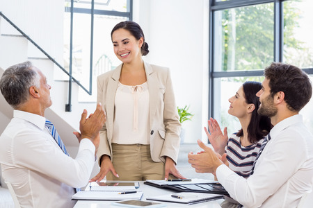 applauding: A businesswoman is standing in front of her colleagues who are applauding at work Stock Photo