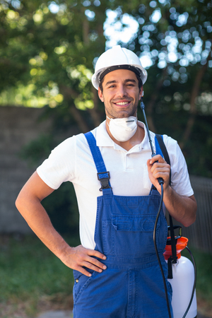 insecticide: Portrait of confident insecticide worker standing in back yard Stock Photo