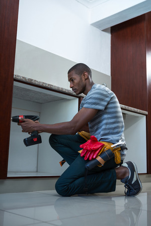 man power: Manual worker drilling a hole in kitchen at home