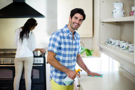 Pulizia della cucina e la donna la cottura dei cibi in background a casa Man Archivio Fotografico - 54785426