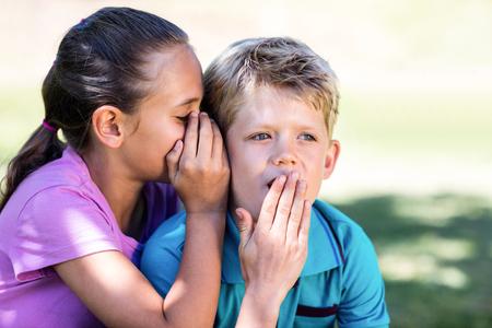 secrete: Girl whispering in her brothers ear in park