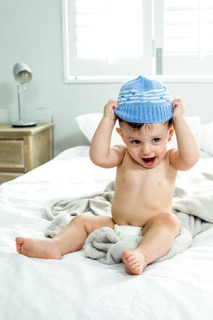 niño sin camisa: Longitud total de descamisado lindo niño llevaba sombrero de punto en la cama