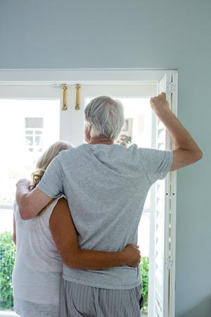 looking through window: Rear view of senior couple looking through window at home