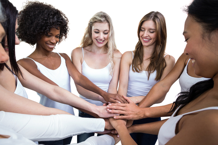 Women in a circle putting their hands together on white background