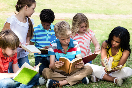 passtime: Children reading book in the park on a sunny day