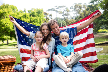 Happy family holding american flag in the park on a sunny day Stock Photo