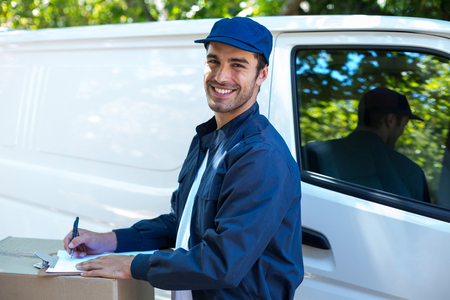 person writing: Portrait of happy delivery person writing in clipboard while standing by van