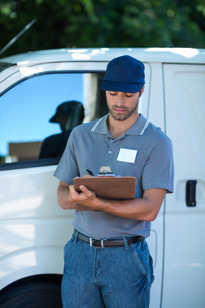 person writing: Delivery person writing in clipboard while standing by van