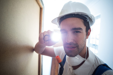 Close-up portrait pest worker with flashlight in hallway at home Stock Photo