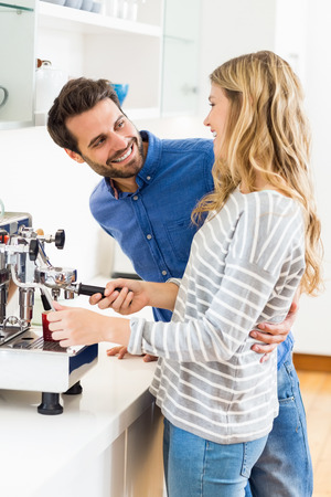 coffeemaker: Young couple preparing coffee from coffeemaker at home Stock Photo