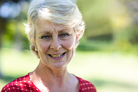 the ageing process: Portrait of smiling senior woman in park Stock Photo