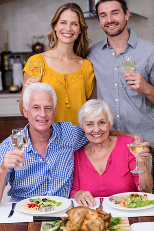 two generation family: Portrait of a two generation family posing with a glass of wine near the dinner table