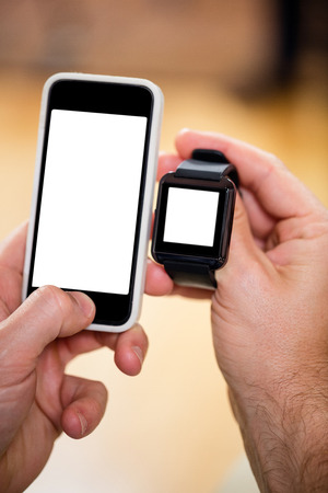 mans watch: Close-up of mans hand holding smart watch and a mobile phone