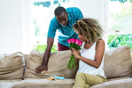 Woman smelling bunch of rosses gifted by man in living room Stock Photo