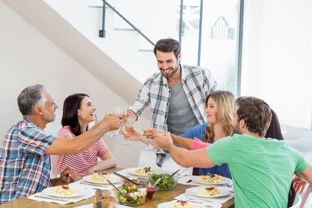 toasting wine: Friends toasting wine glasses while having a meal at dining table Stock Photo