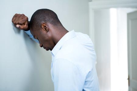 persona triste: Hombre tensado que se inclina en la pared en el país