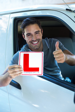 l plate: Portrait of handsome man showing thumbs up while holding L plate in car Stock Photo