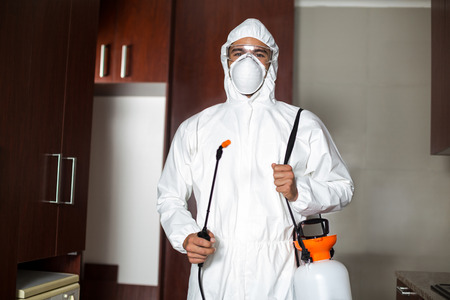 protective suit: Portrait of pest worker in protective suit standing at home Stock Photo