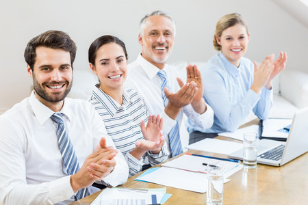 applauding: Business colleagues applauding in a meeting at office