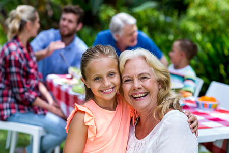 carrying girl: Portrait of smiling granny carrying girl during breakfast at yard Stock Photo
