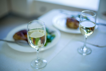 domicile: Two wine glasses and meal on table at home Stock Photo