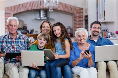 multigeneration: Multi-generation family using a laptop, tablet and phone at home