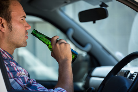 drinking driving: Man drinking beer while driving car