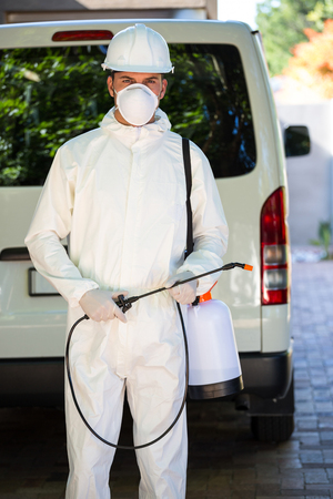 crop sprayer: Pest control man in protective workwear standing behind a van Stock Photo