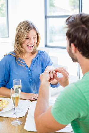 gifting: Man gifting finger ring to his woman at home Stock Photo