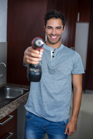 hand drill: Portrait of smiling man holding cordless hand drill at home