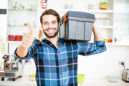 domiciles: Portrait of man carrying tool box giving thumbs up in the kitchen