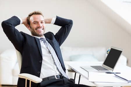 happy businessman: Portrait of happy businessman relaxing in office