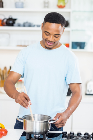 home cooking: Man preparing a meal in kitchen at home