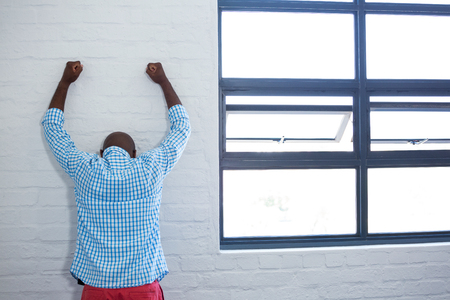 rea: Rea view of upset man leaning against wall in office