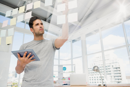 Man holding digital tablet and looking at sticky notes in the office