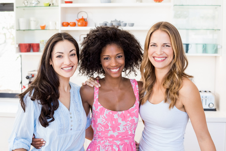 arm around: Portrait of beautiful women standing with arm around in kitchen at home