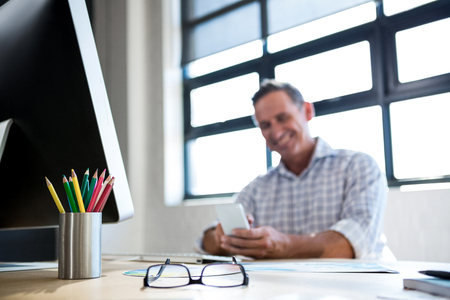 pen holder: Spectacle and pen holder on desk in office and man using mobile phone in background Stock Photo