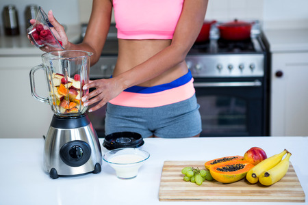 mid section: Mid section of a woman preparing fruit smoothie in blender