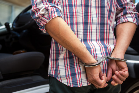 handcuffed: Rear view of man handcuffed behind his back