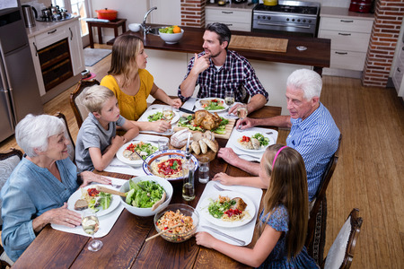 Multi-generation family talking while having meal in kitchen at home