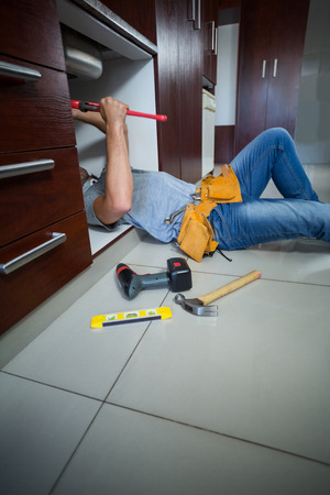 pipe wrench: Midsection of man using pipe wrench in kitchen Stock Photo