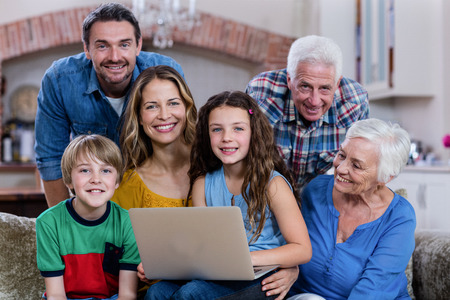multigeneration: Multi-generation family sitting on sofa and using laptop at home