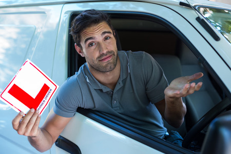 l plate: Portrait of handsome man shrugging while holding L plate in car