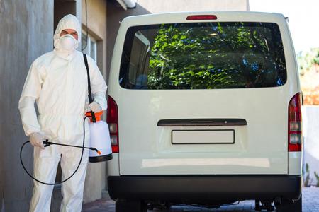 Schädlingsbekämpfung Mann in Schutzkleidung, die hinter einem Lieferwagen