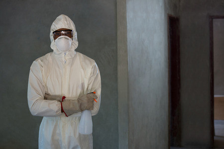 spray bottle: Pest control man standing with spray bottle in home
