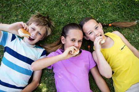 friendliness: Retrato de los niños tirado en la hierba y comer el bollo