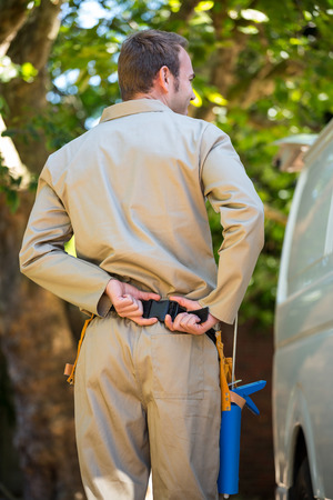 tool belt: Rear view of handyman with tool belt around waist standing next to delivery van