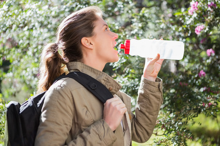 break in: Woman drinking water while doing a break in the countryside Stock Photo