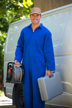 tool box: Portrait of mechanic with a tool box and cable standing near a car Stock Photo