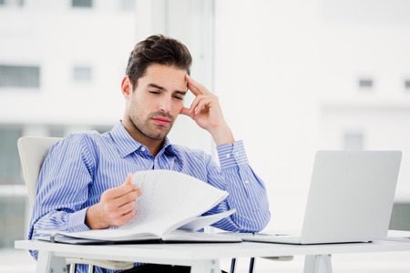 worried businessman: Worried businessman looking at diary in office Stock Photo